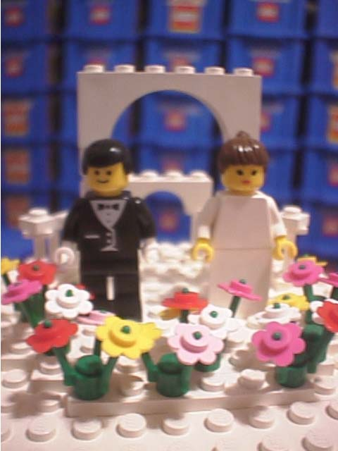 The minifig bride and groom atop the cake Four different colors of flowers